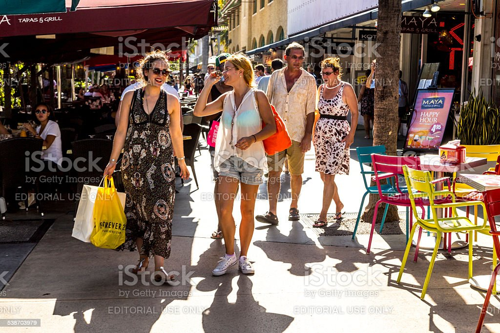 people go shopping in the afternoon sun in Lincoln Road stock photo