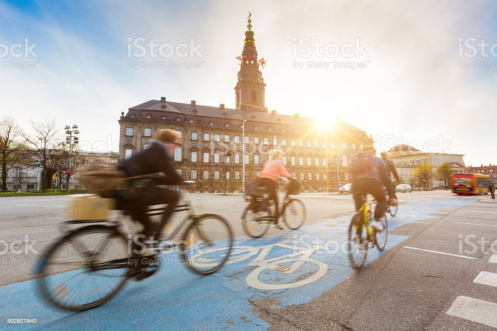 Blurred people going by bike in Copenhagen, with Christiansborg...