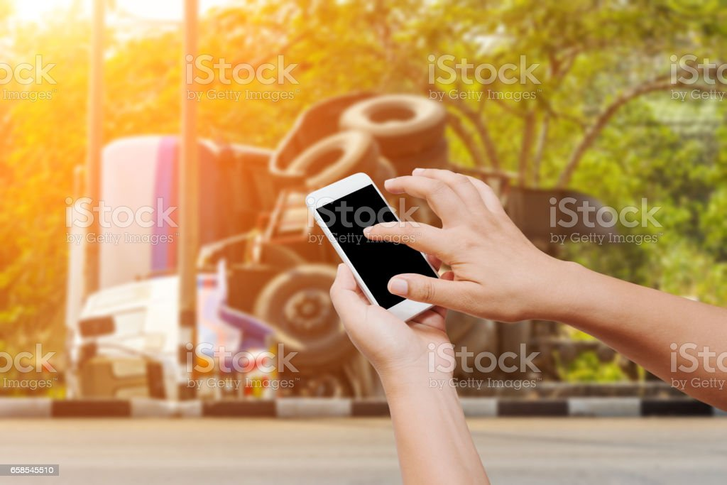 people hand hold and touch screen smart phone on overturned truck accident background stock photo