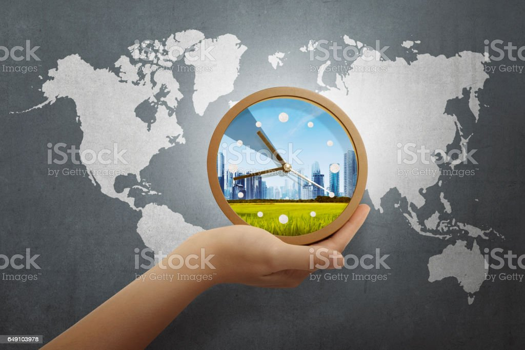 People hand holding clock with world map stock photo