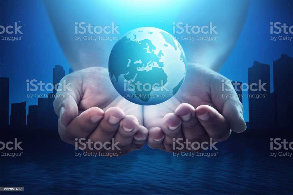 People hand holding floating earth with silhouette cityscape stock photo