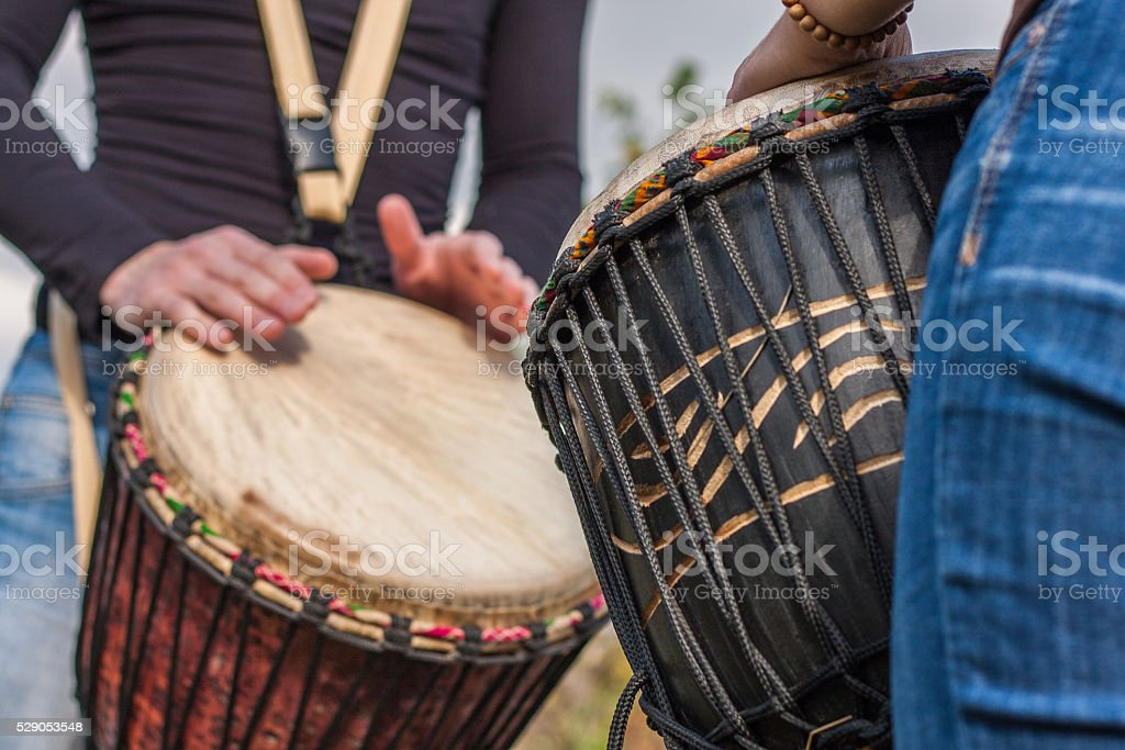 People hands playing music at djembe drums stock photo