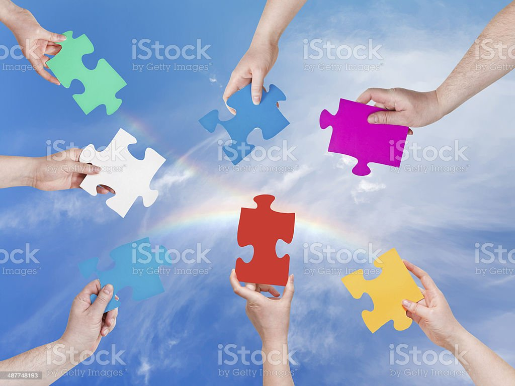 people hands with puzzle pieces with rainbow stock photo