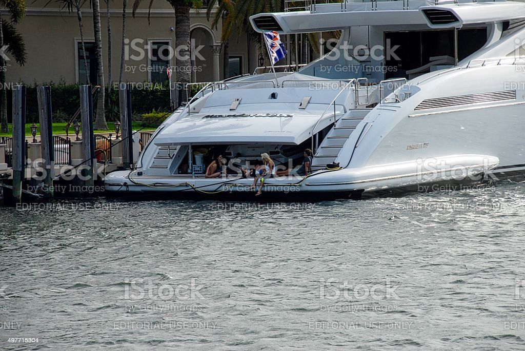 People Hanging Out on Mega Yacht Moored at Dock stock photo