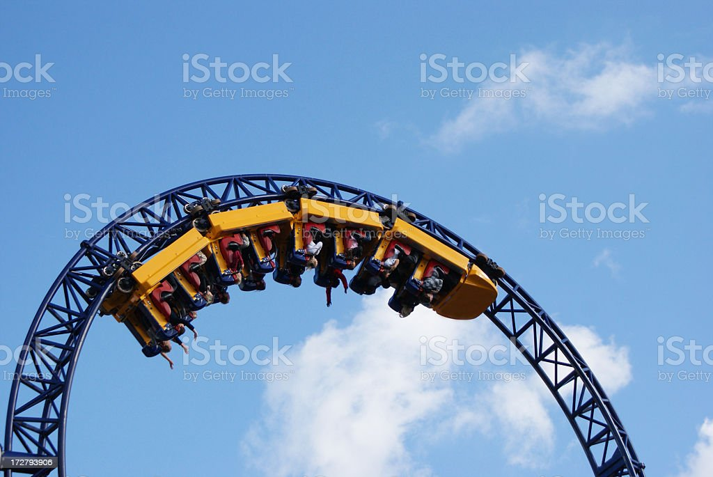 People hanging upside down on the roller coaster track stock photo