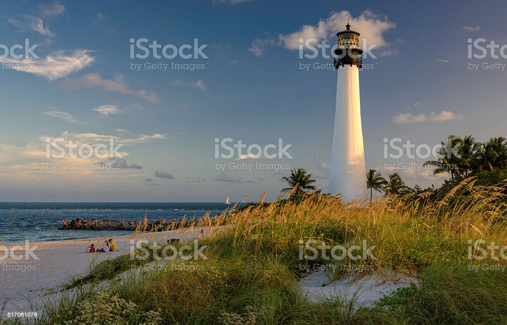 People have a rest on a beach, near a  Lighthouse. stock photo