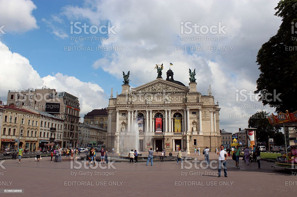people having a rest besides opera-house in Lviv stock photo