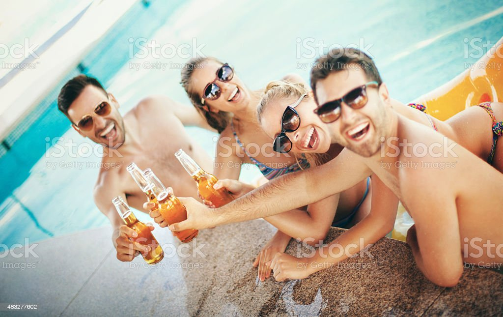 People having beers at poolside. stock photo