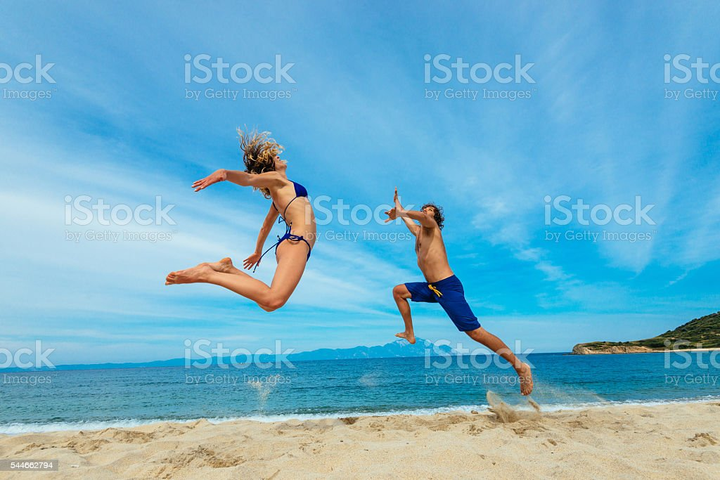 People having fun at beach in summer, jumping on sand stock photo