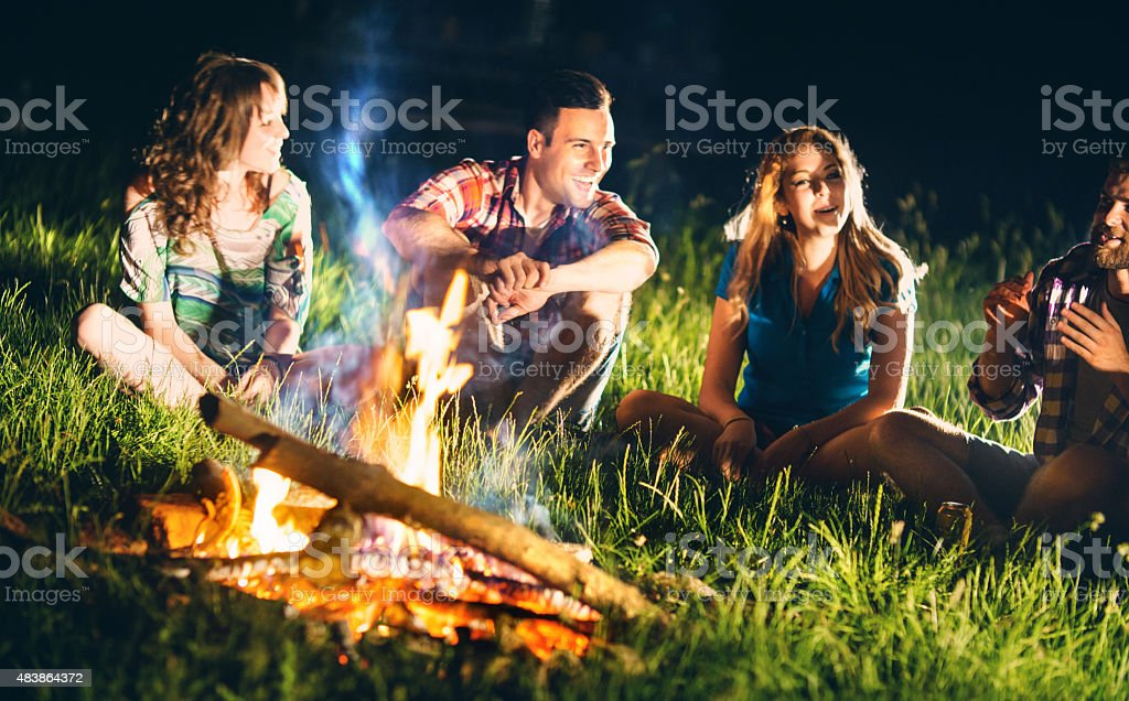 People having fun by campfire. stock photo