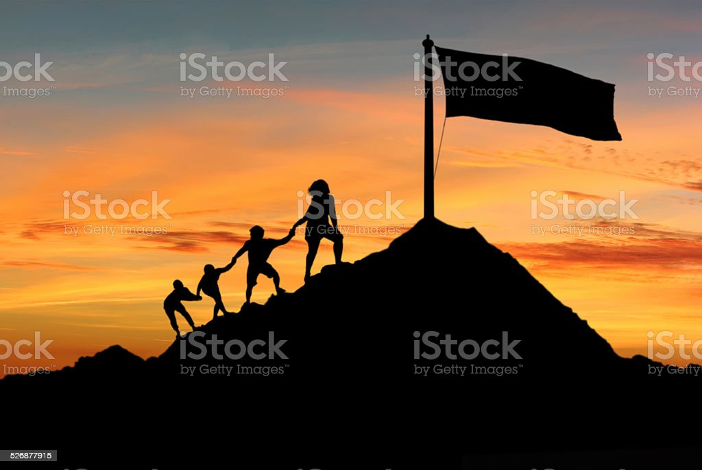People helping each other to reach top of the mounting stock photo