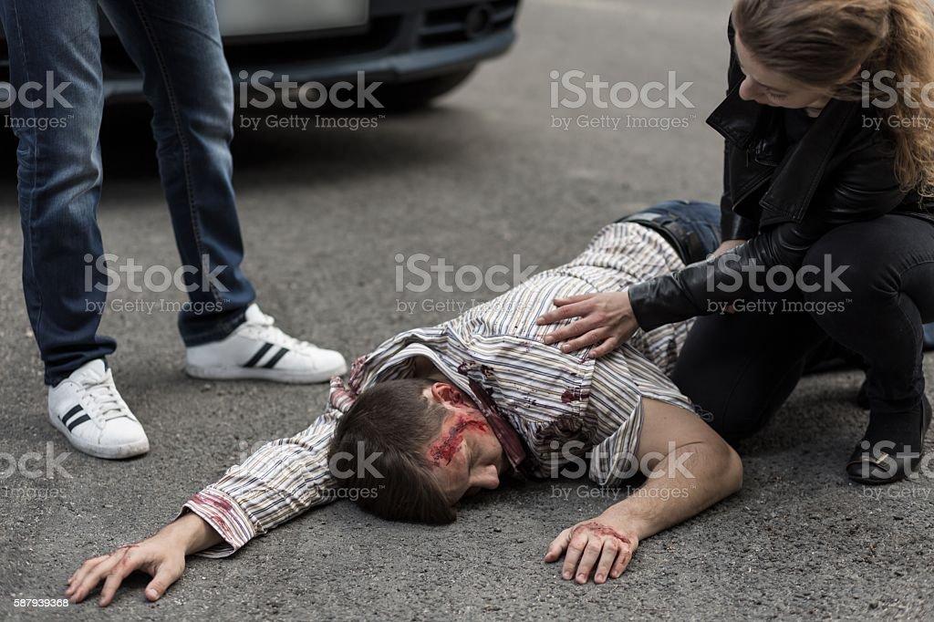 People helping injured man stock photo