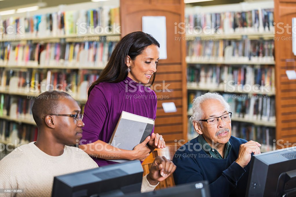 People helping senior man use computer in library stock photo