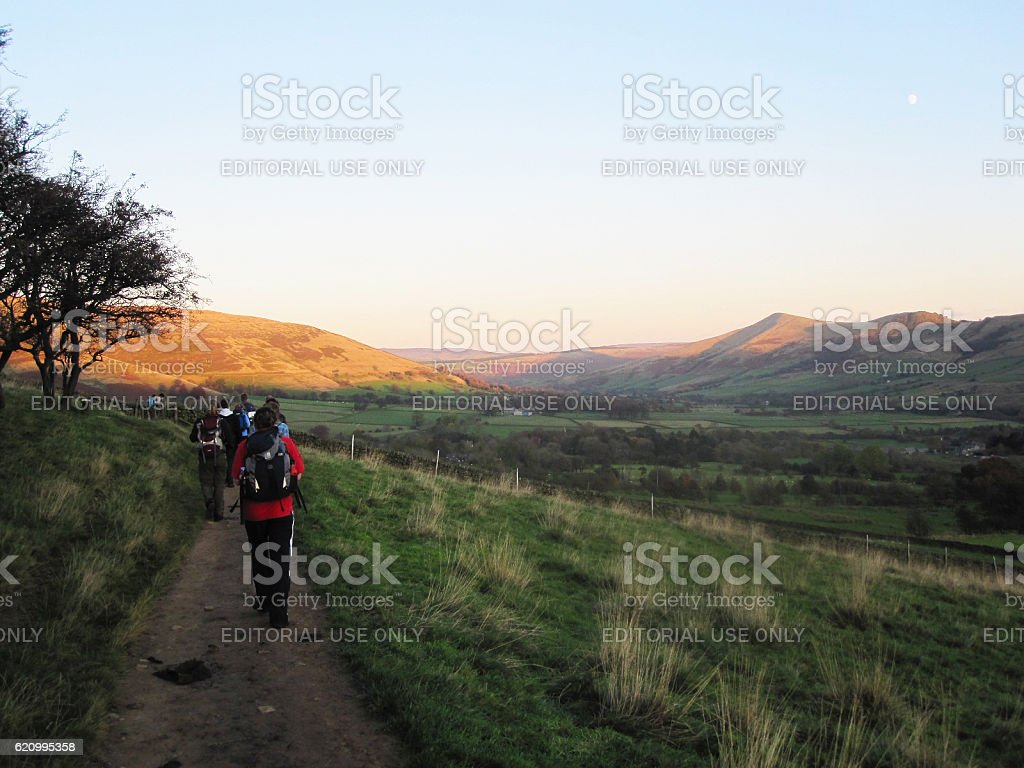 People hiking in Peak District during sunset stock photo