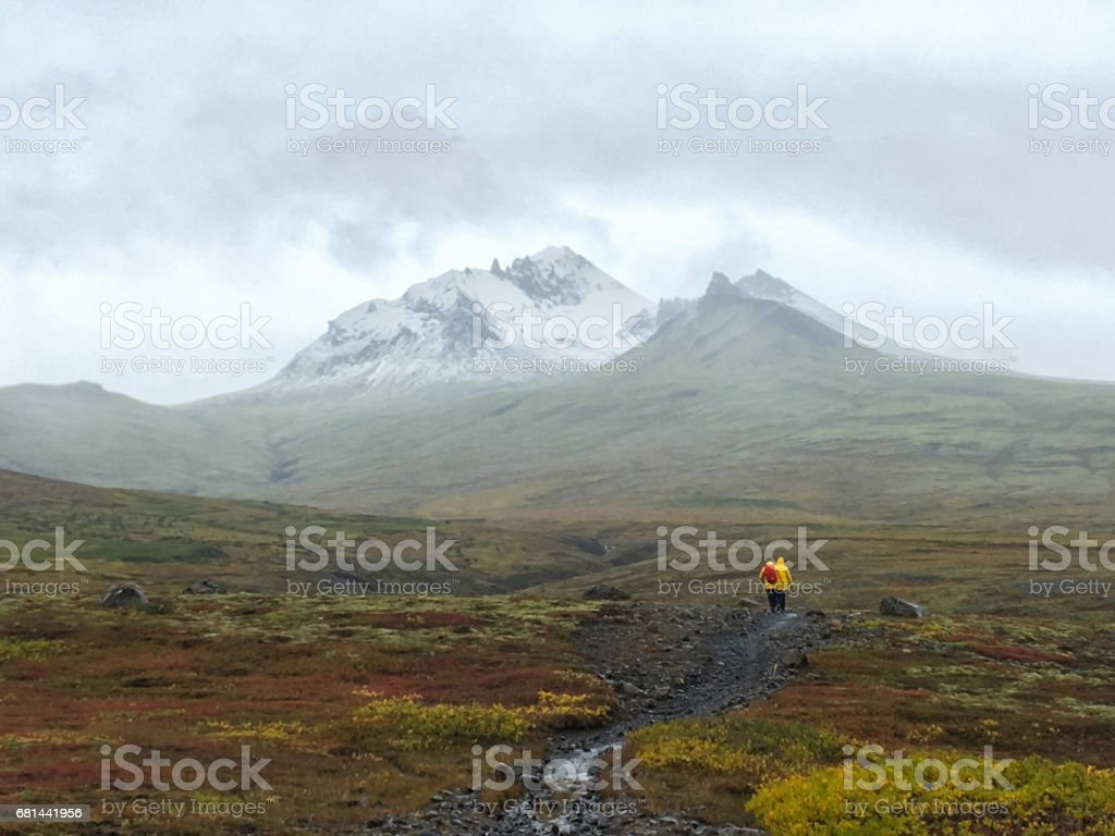 People hiking to the glacier. Tough, cold and wet weather. Wind, a lot of rain. View over mountain range. View to the glacier with ice and snow. Water drops on the lense. stock photo