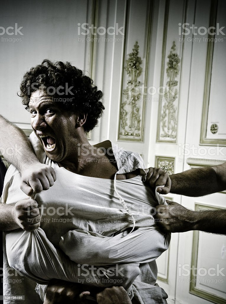People Holding Angry Young Man in Straight Jacket royalty-free stock photo