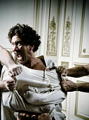 People Holding Angry Young Man in Straight Jacket