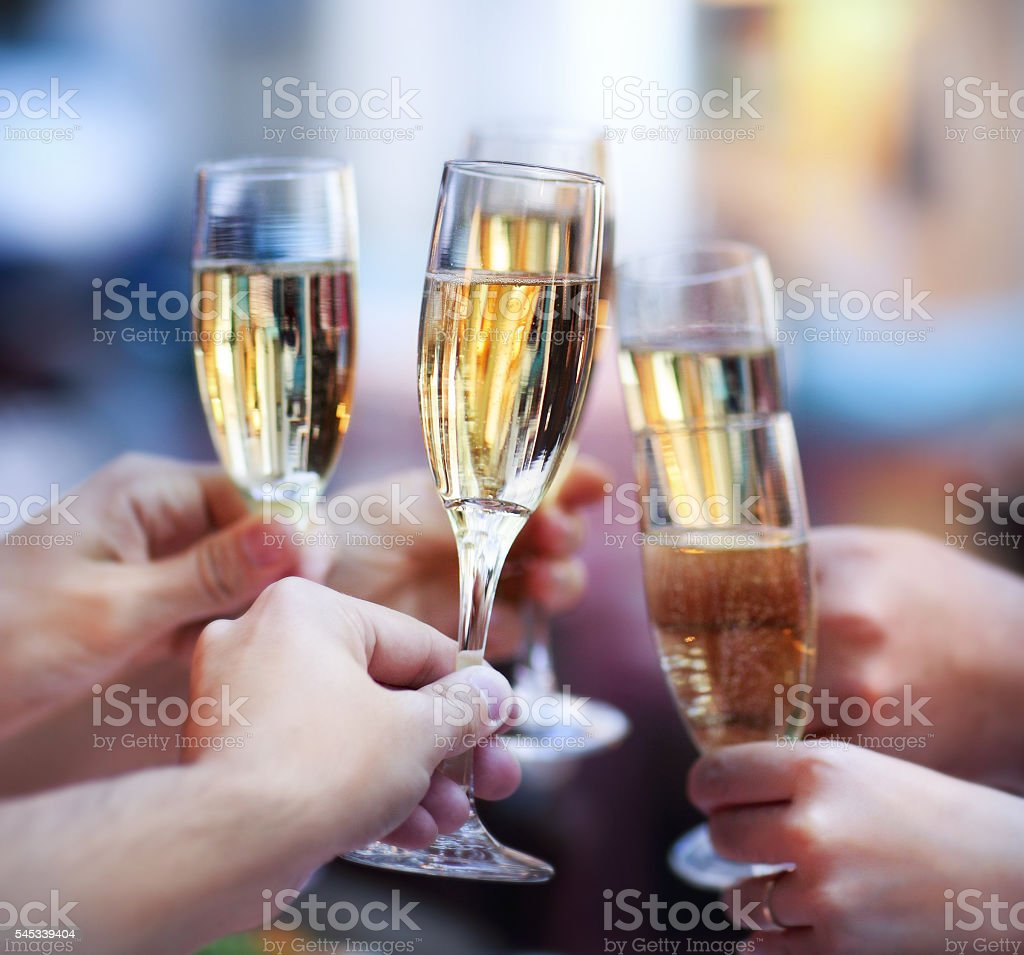 People holding glasses of champagne making a toast stock photo