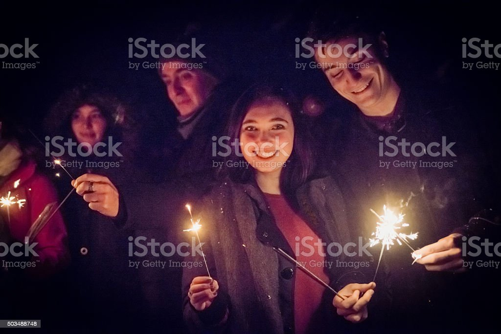 People holding sparkling Bengal fire outdoors at night in winter. stock photo