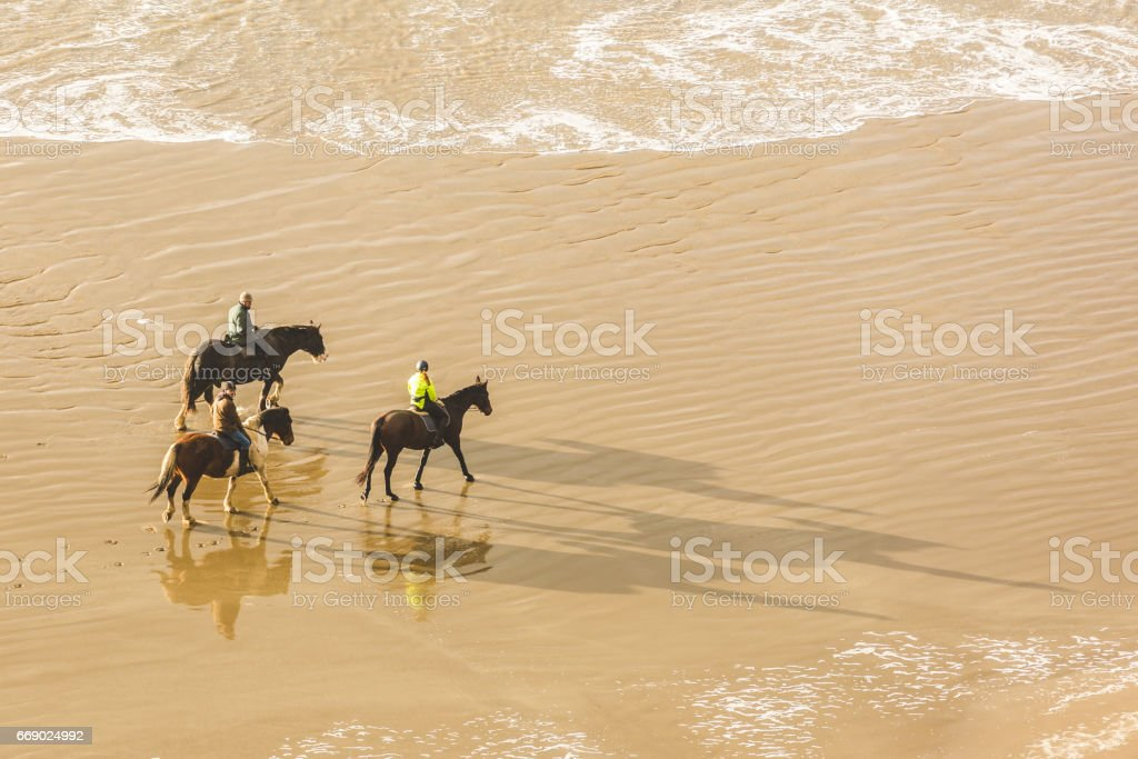 People horse riding on the beach, aerial view stock photo