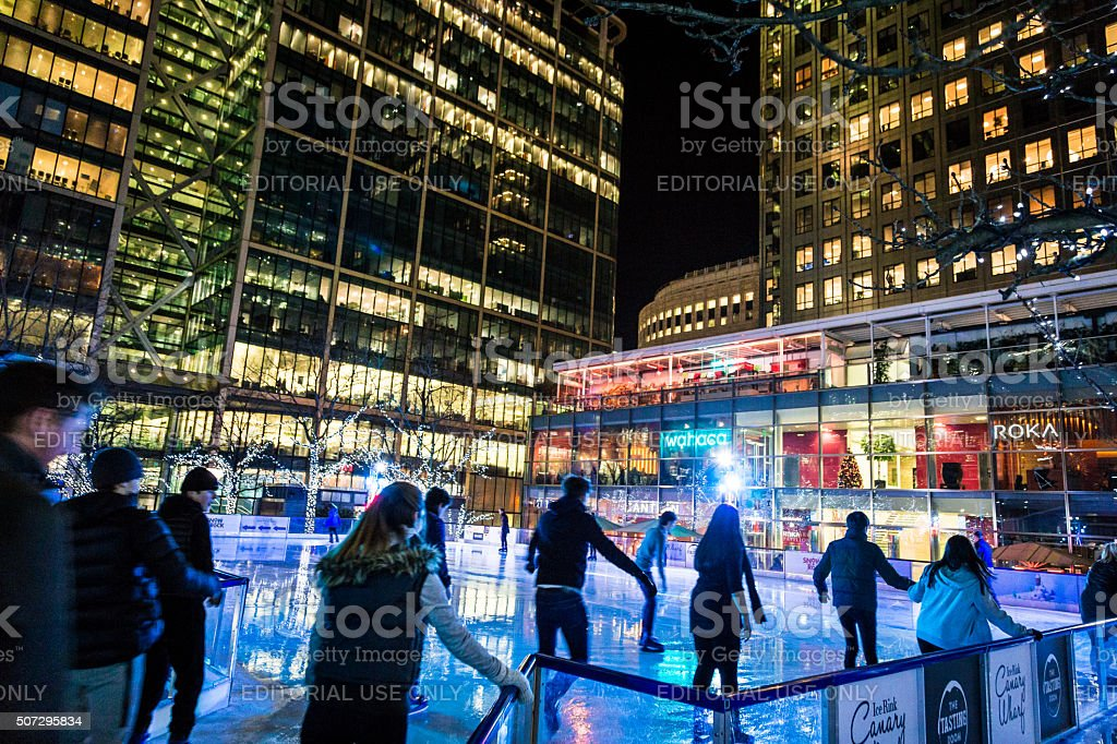 People ice skating at Canary Wharf ice rink, London, UK stock photo
