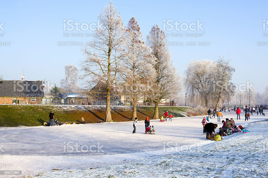 People Ice skating on frozen canal. stock photo
