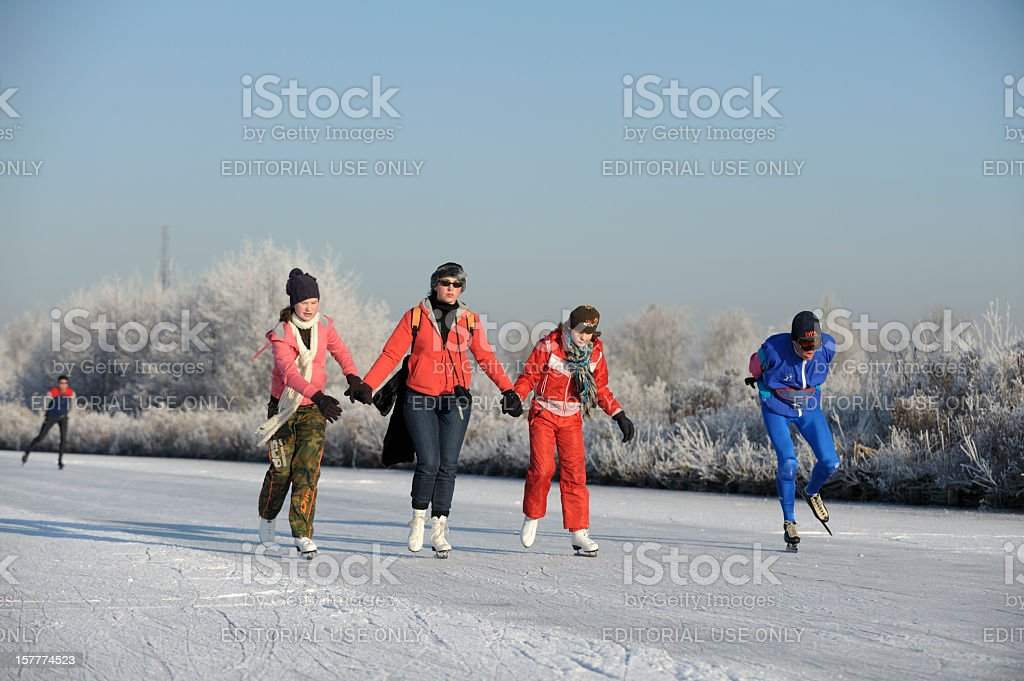 People ice-skating on a lake in the Netherlands royalty-free stock photo