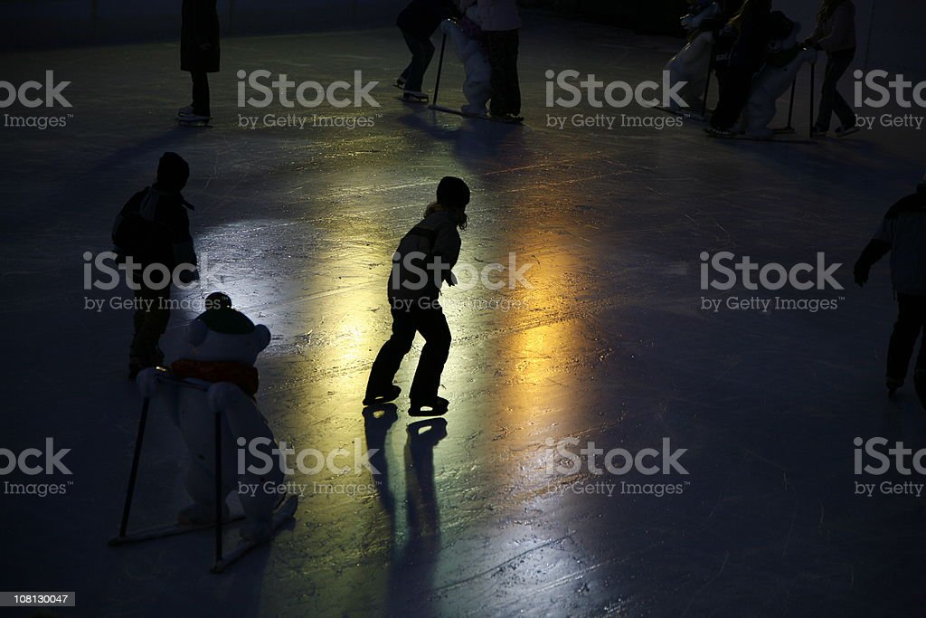 People Ice-Skating on Rink at Night stock photo
