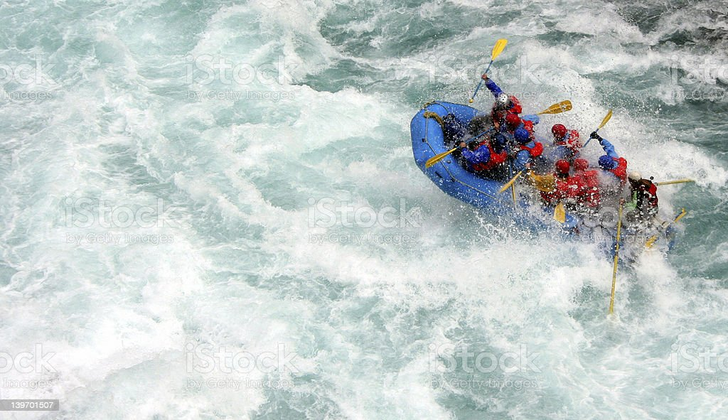 People in a blue inflatable boat river rafting royalty-free stock photo