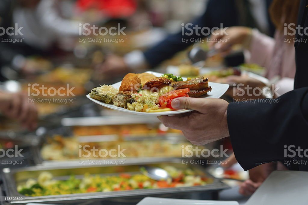 People in a buffet line with full plates stock photo