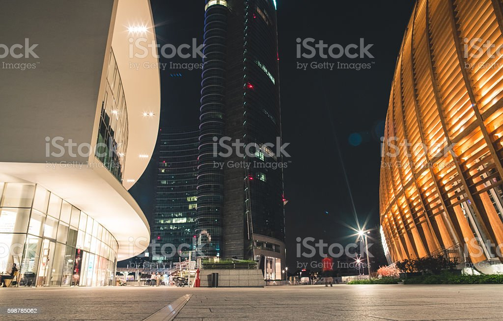 People in a modern plaza with futuristic buildings by night stock photo