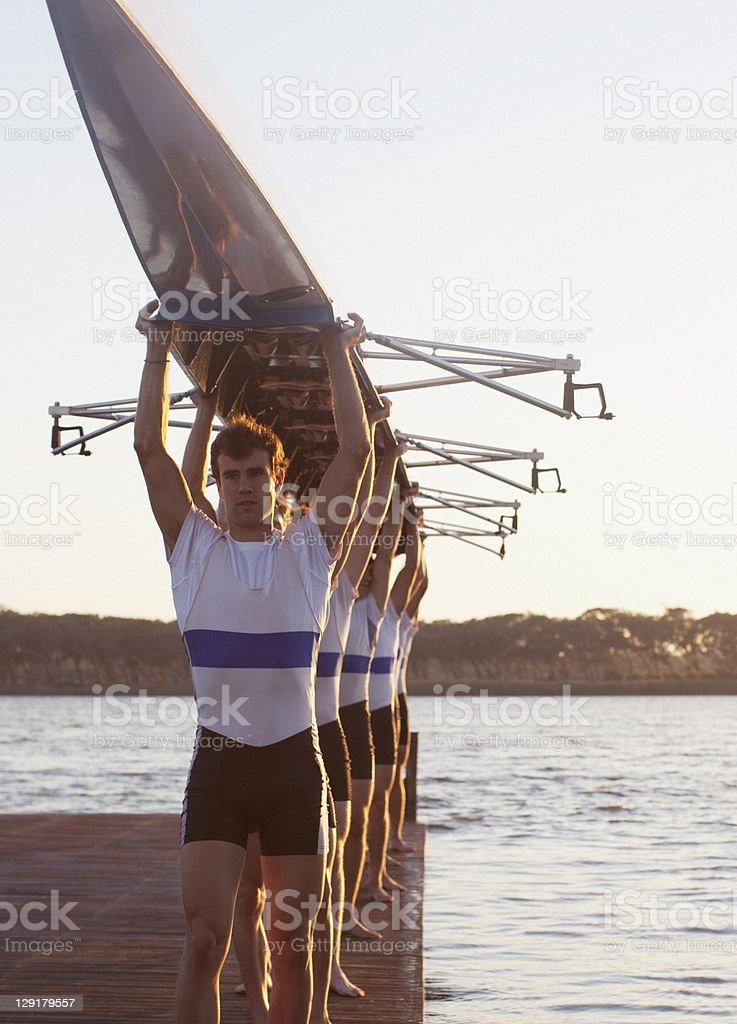 People in a row holding canoe upwards royalty-free stock photo