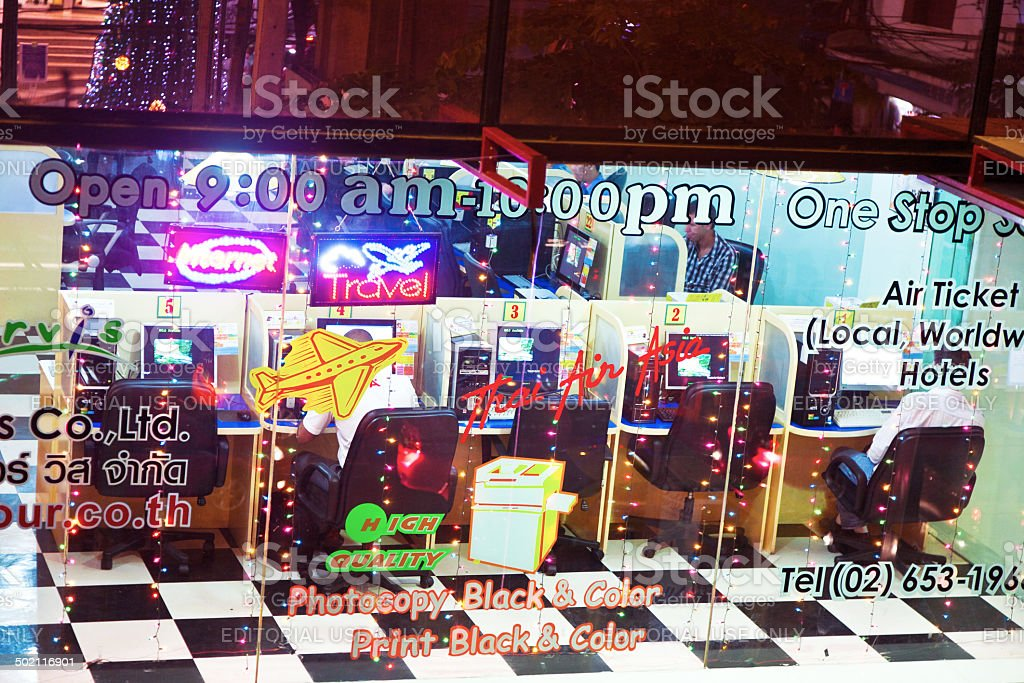 people in an internet cafe which also offers travelservices stock photo