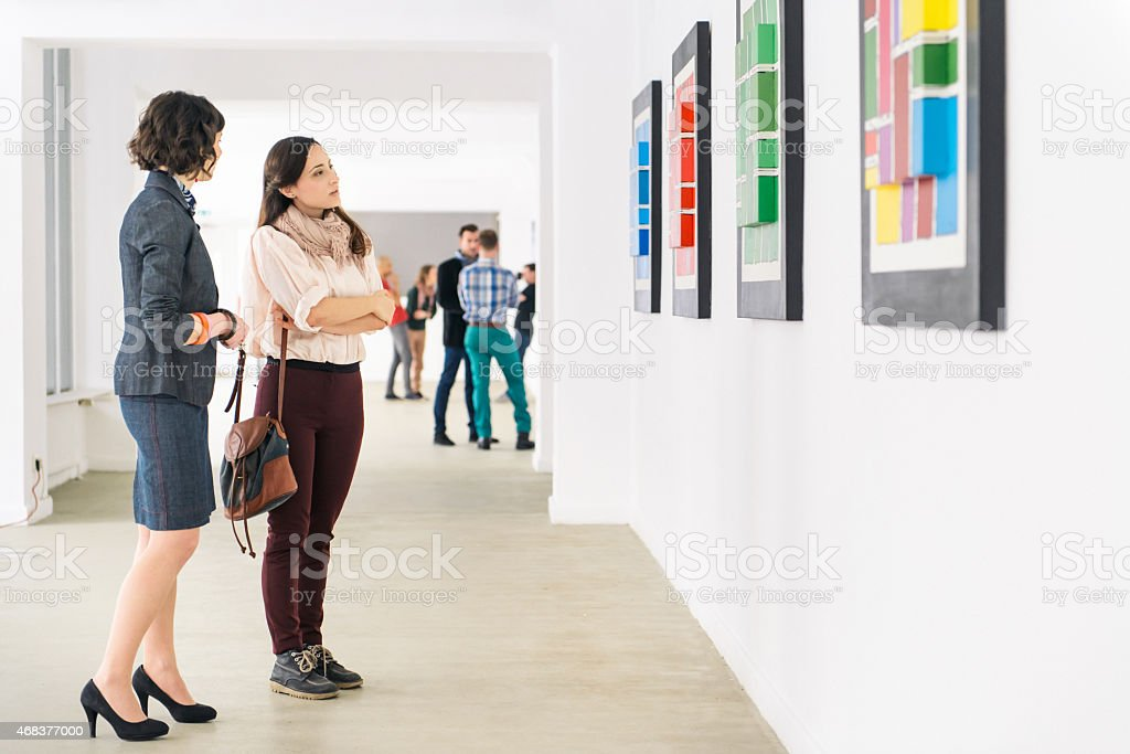People in an art gallery looking at artwork. It\'s a gallery opening...