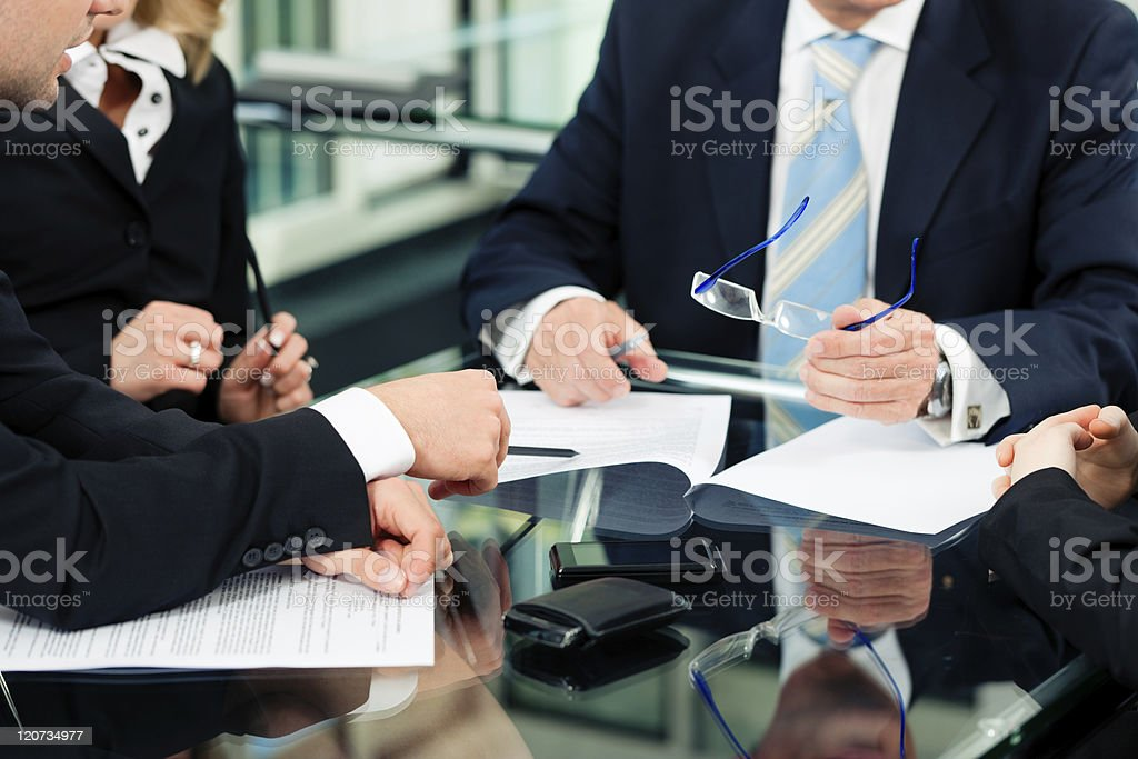 People in business suits with paperwork at desk stock photo