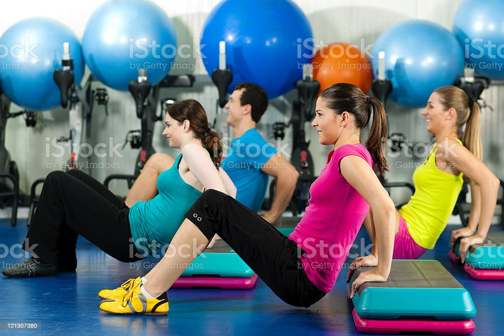 People in gym on step board stock photo