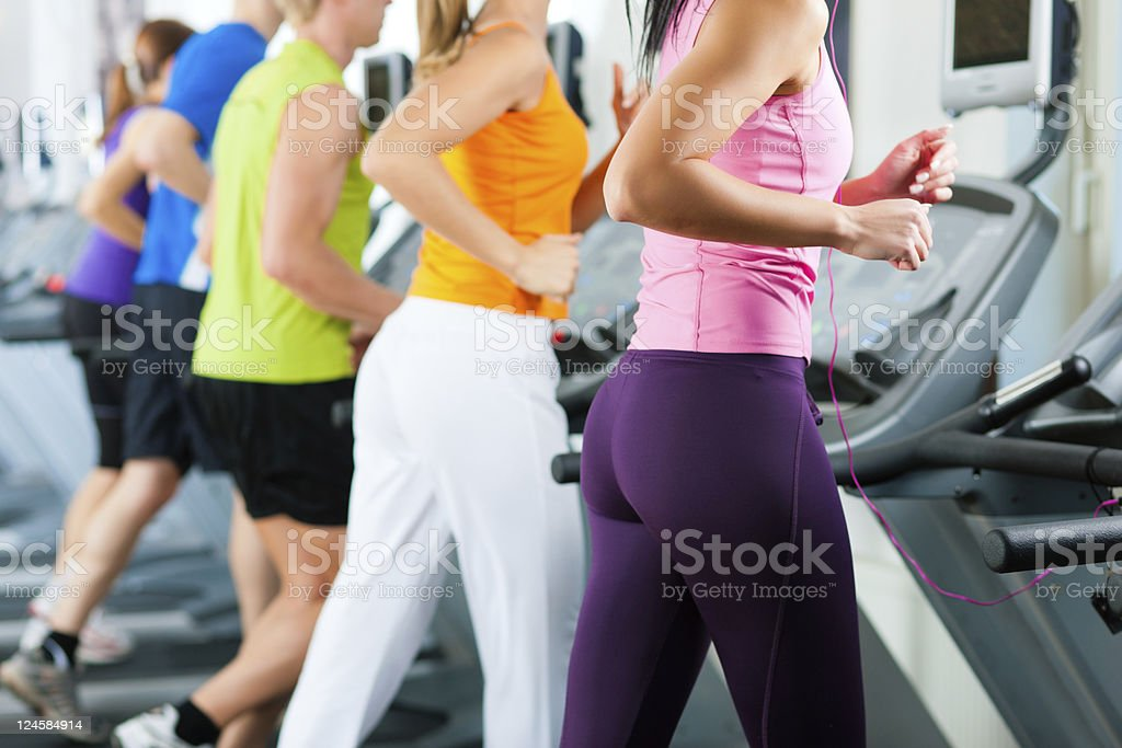 People in gym on treadmill running royalty-free stock photo