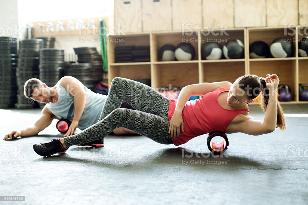 People in gym using support roller stock photo