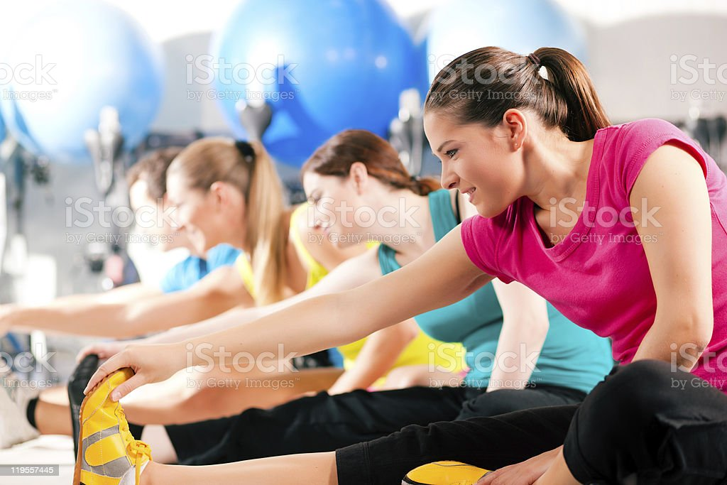 People in gym warming up stretching stock photo