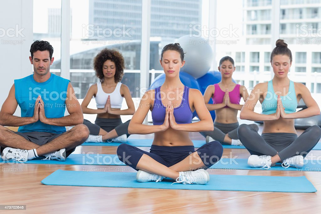 People in Namaste position with eyes closed at fitness studio stock photo