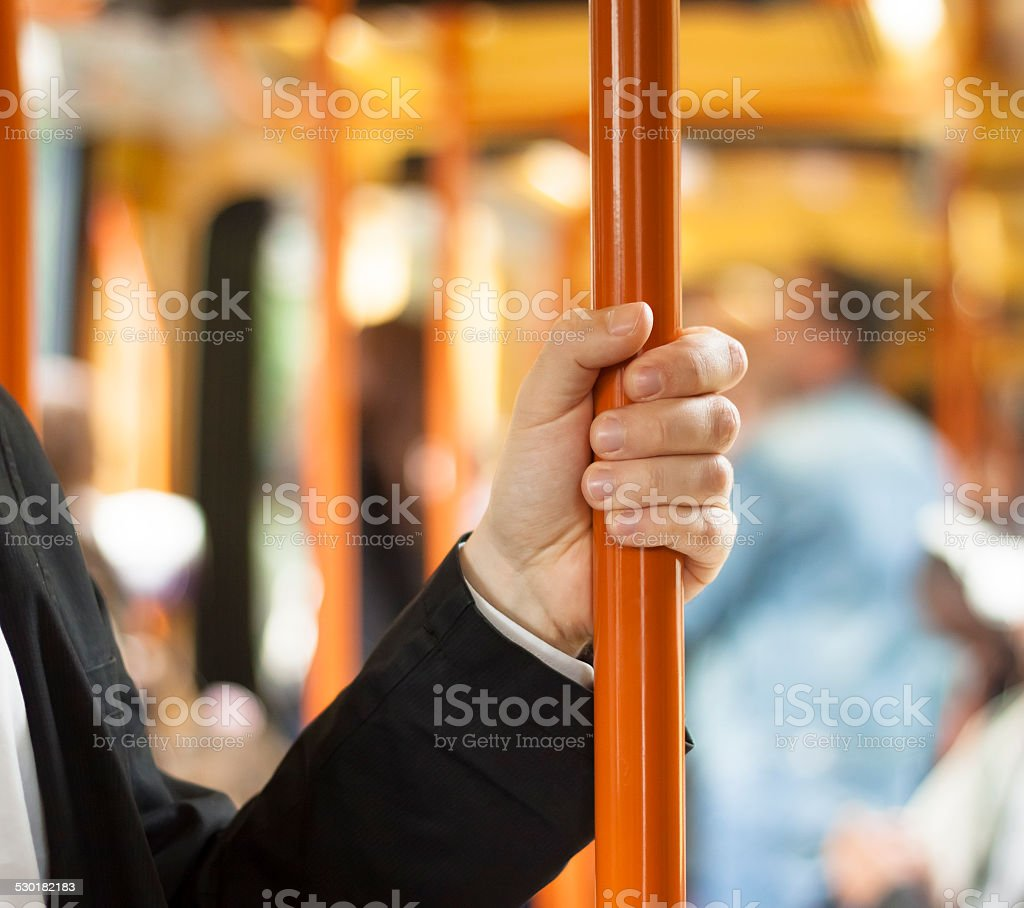 people in public transport, hand holding handgrip stock photo