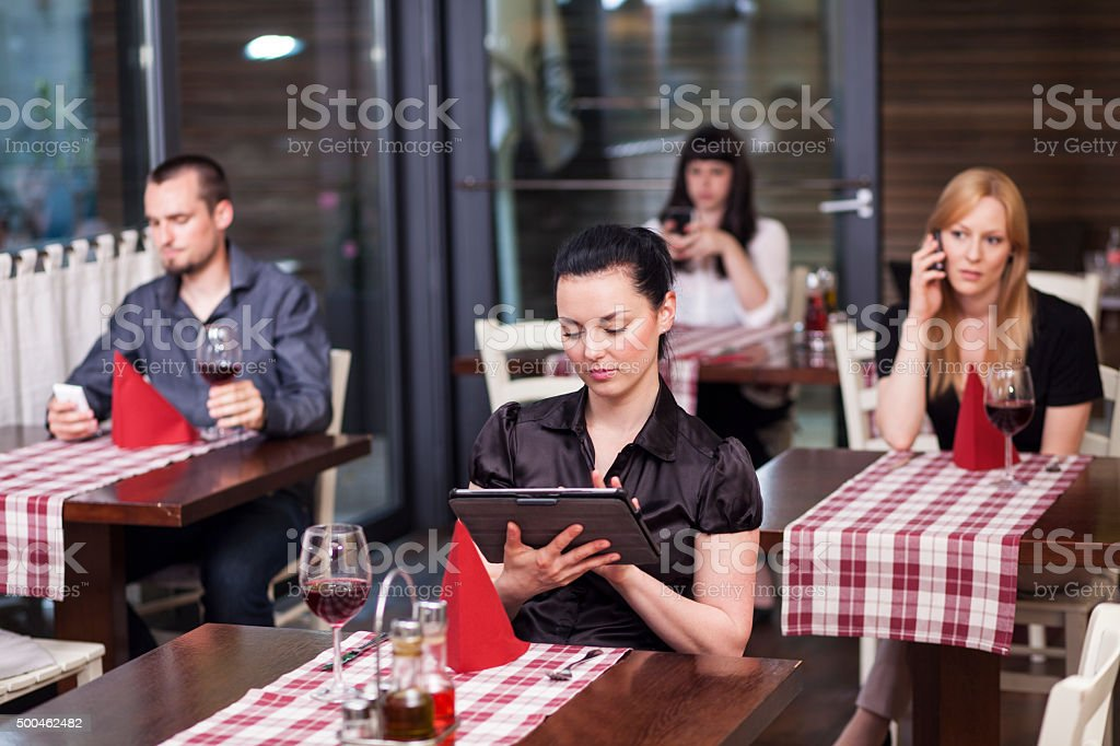 People in restaurant all using communication technology stock photo