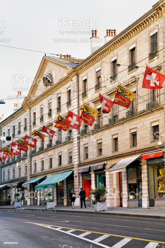 People in Rue Corraterie Street with flags in Geneva Swiss stock photo