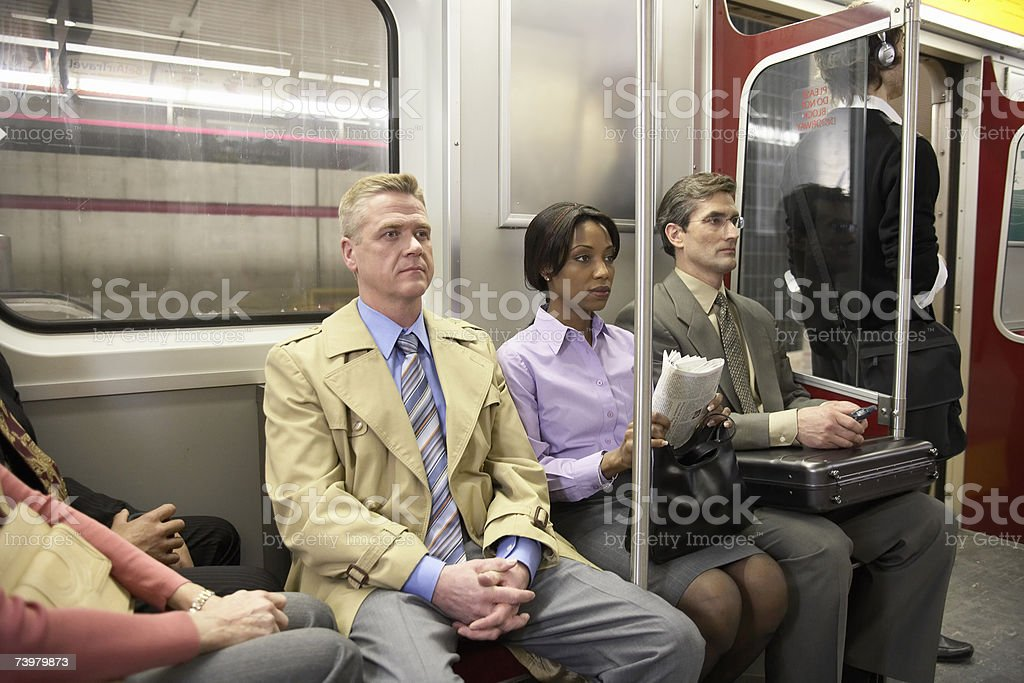 People in subway train, sitting side by side stock photo
