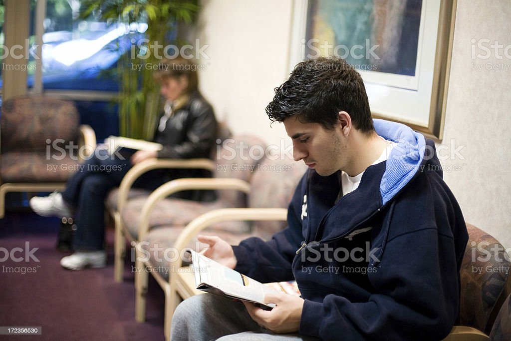 people in waiting room reading magazines royalty-free stock photo