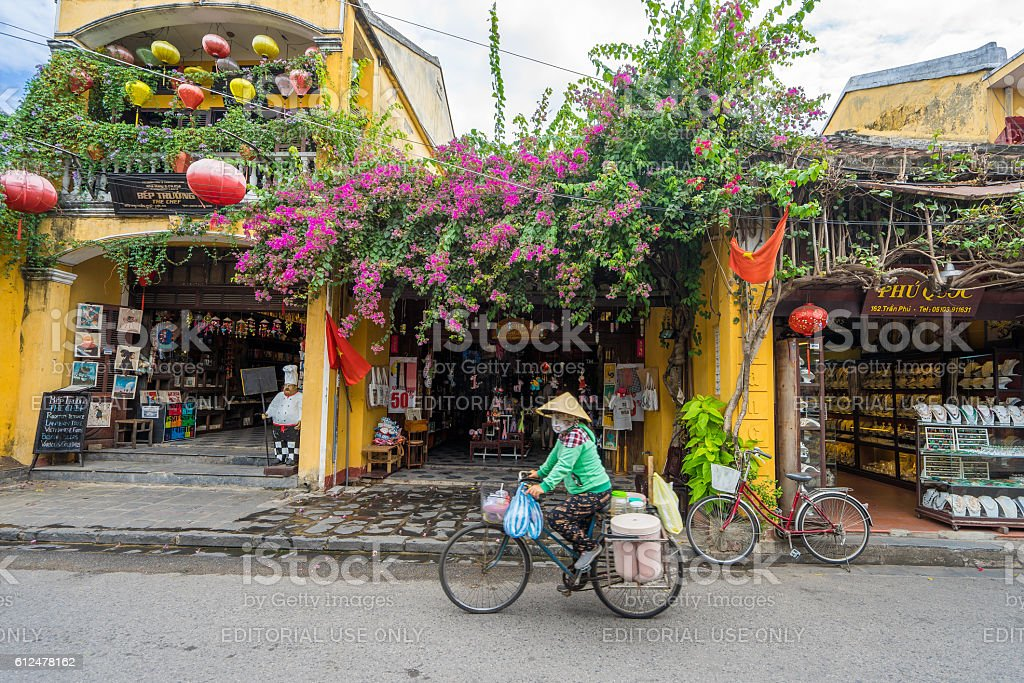 People is riding on bicycle on Hoi An street stock photo