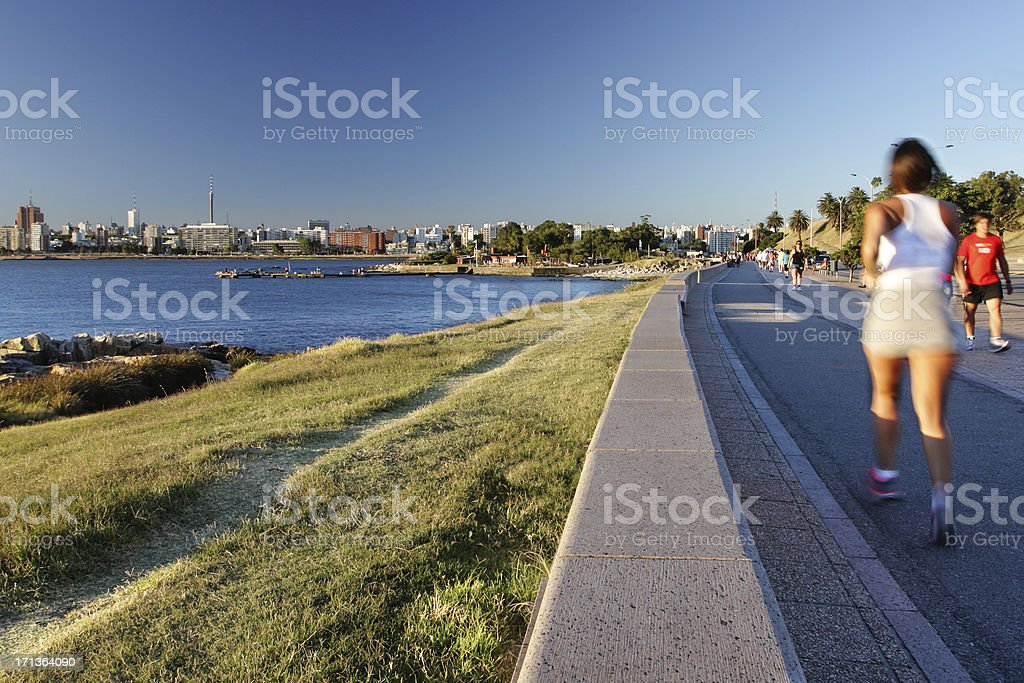 People jogging at the riverside with Montevideo cityscape background stock photo