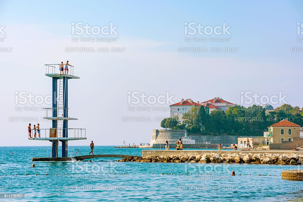 People jumping into the sea stock photo