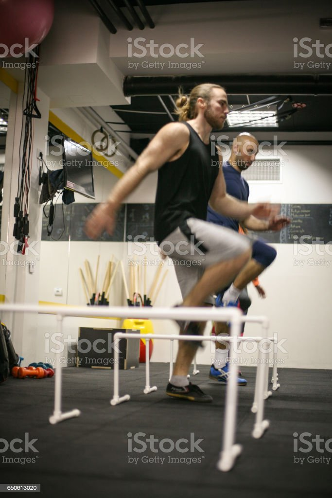 People jumping over obstacles in gym. stock photo