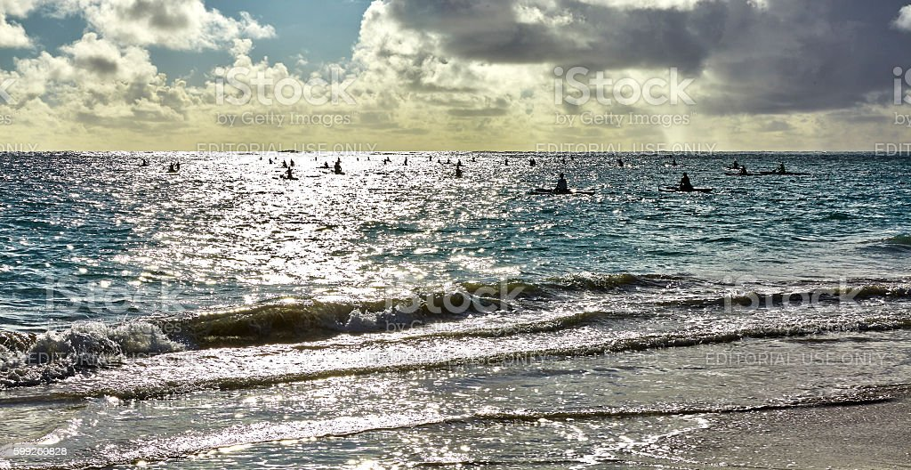 People kayak over ocean shore surf at sunrise in Hawaii stock photo